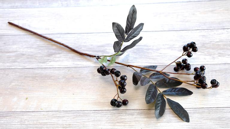 黒っぽい葉と黒いふっくらした実のブランチベリーのアーティフィシャルフラワー。