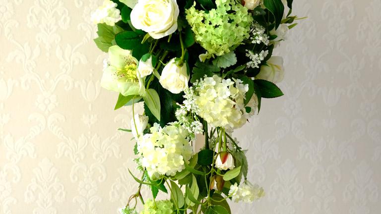 リキュウソウを使ったアーティフィシャルフラワーのキャスケードブーケ。白いバラやグリーンのあじさいが入ってみずみずしい様子。