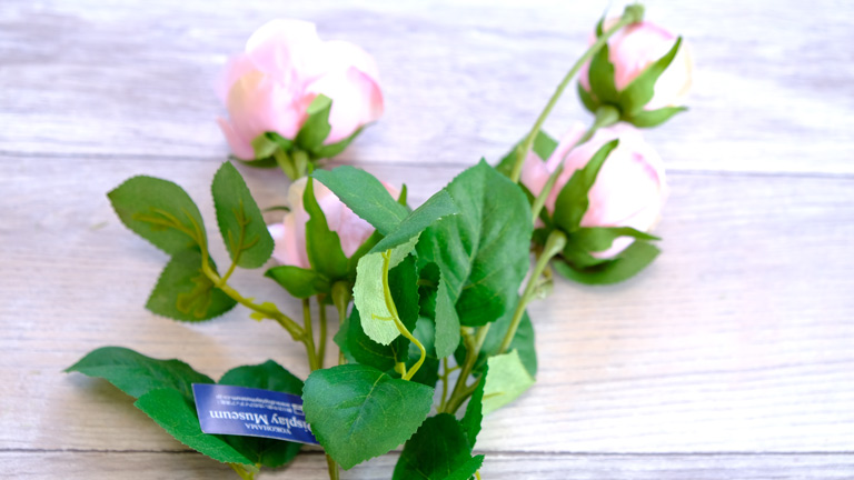 ライトピンクの少しころんとした形の造花のバラ。