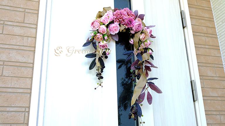 ラムズイヤーを使った玄関の壁掛けの花。青みピンクの上品なバラと黒い実が特徴。