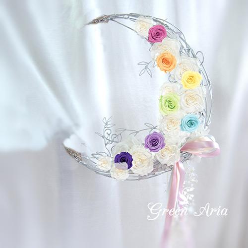 7色のバラを白い三日月に配置した画像