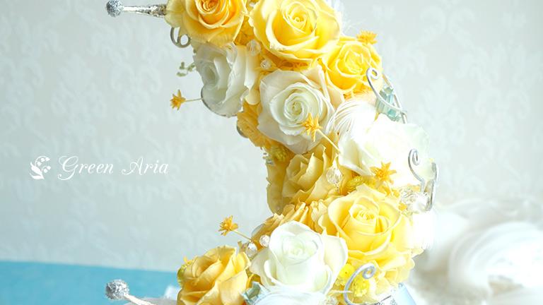 白いバラに黄色のバラ、三日月からは、黄色い小さな星のような花がぴょんぴょん跳んでおり、フワフワの羽根も付いている。ムーンスティックブルーブーケのアップ。