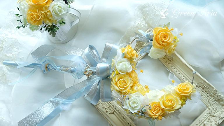 白いドレスの上にアンティークの額縁。額縁の上にそっと置かれたムーンスティックがシャービーシックな印象。落ち着きのあるイエローのグラデーションのバラで出来た三日月が美しい。三日月には、ブルーとシルバーのスティックが付いていてスティック部分を持つウエディングブーケになっている