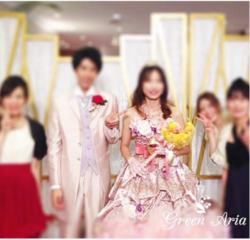 三日月ステッキウエディングブーケとピンクのドレスを着た新婦と新郎