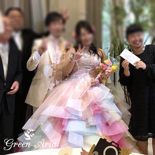 レインボーのドレスにレインボーの三日月ステッキウエディングブーケを持つ新婦
