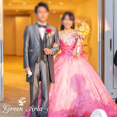 ピンクのドレスを着て、黄色の三日月ステッキウエディングブーケをもって再入場する新郎新婦
