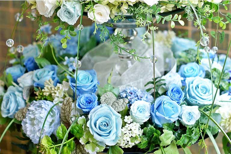 ブルーのグラデーションのバラがグリーンの葉とともにリングになっている