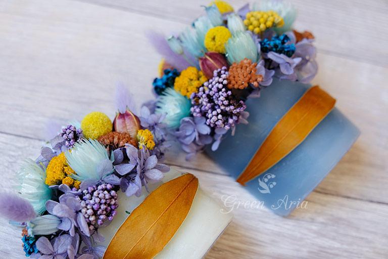 水色と白のキャンドル材料でできた器に紫・ブルー・イエローのドライフラワーをアレンジしている