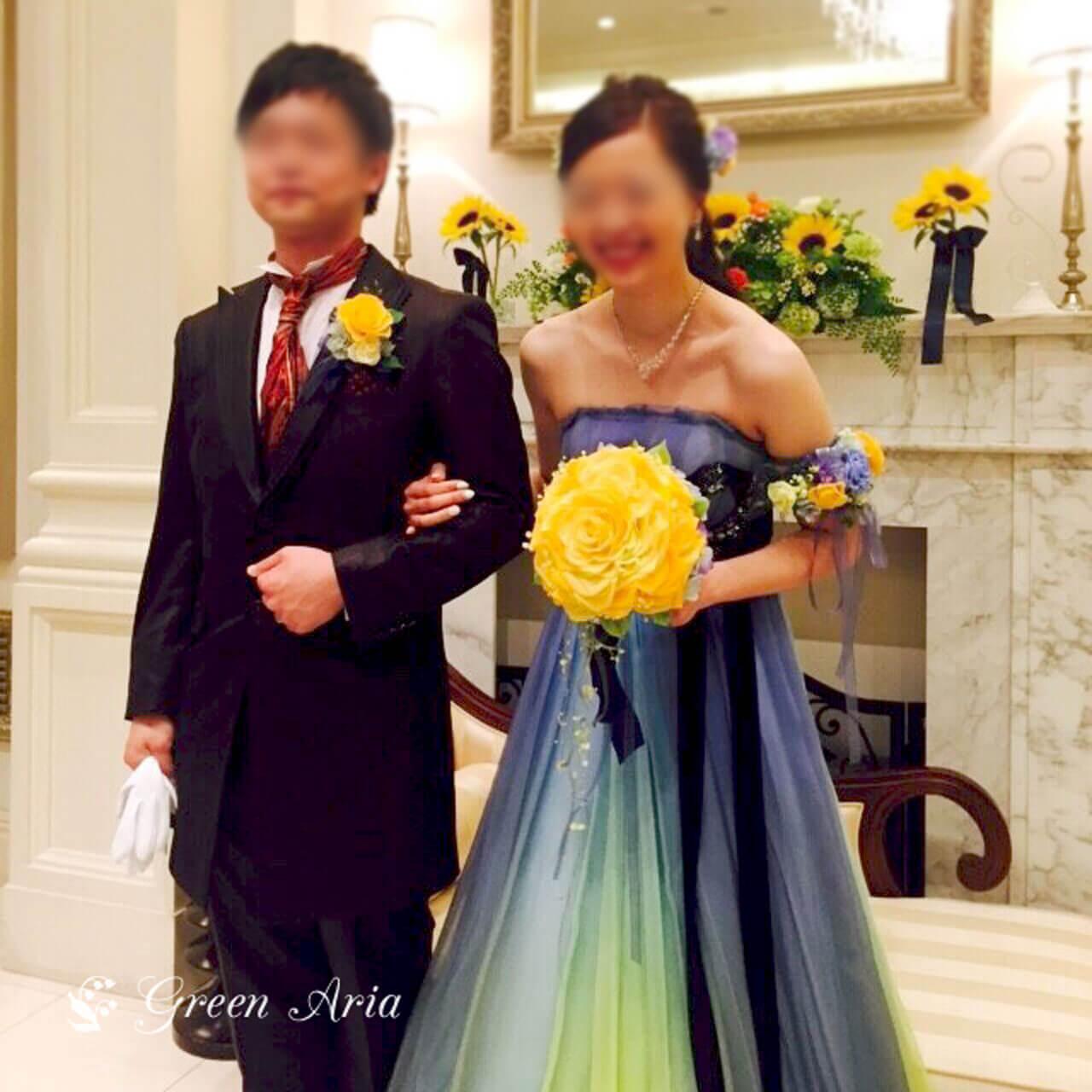 ブルーからイエローのグラデーションドレスを着た新婦はイエローの大きなバラを手に持っている