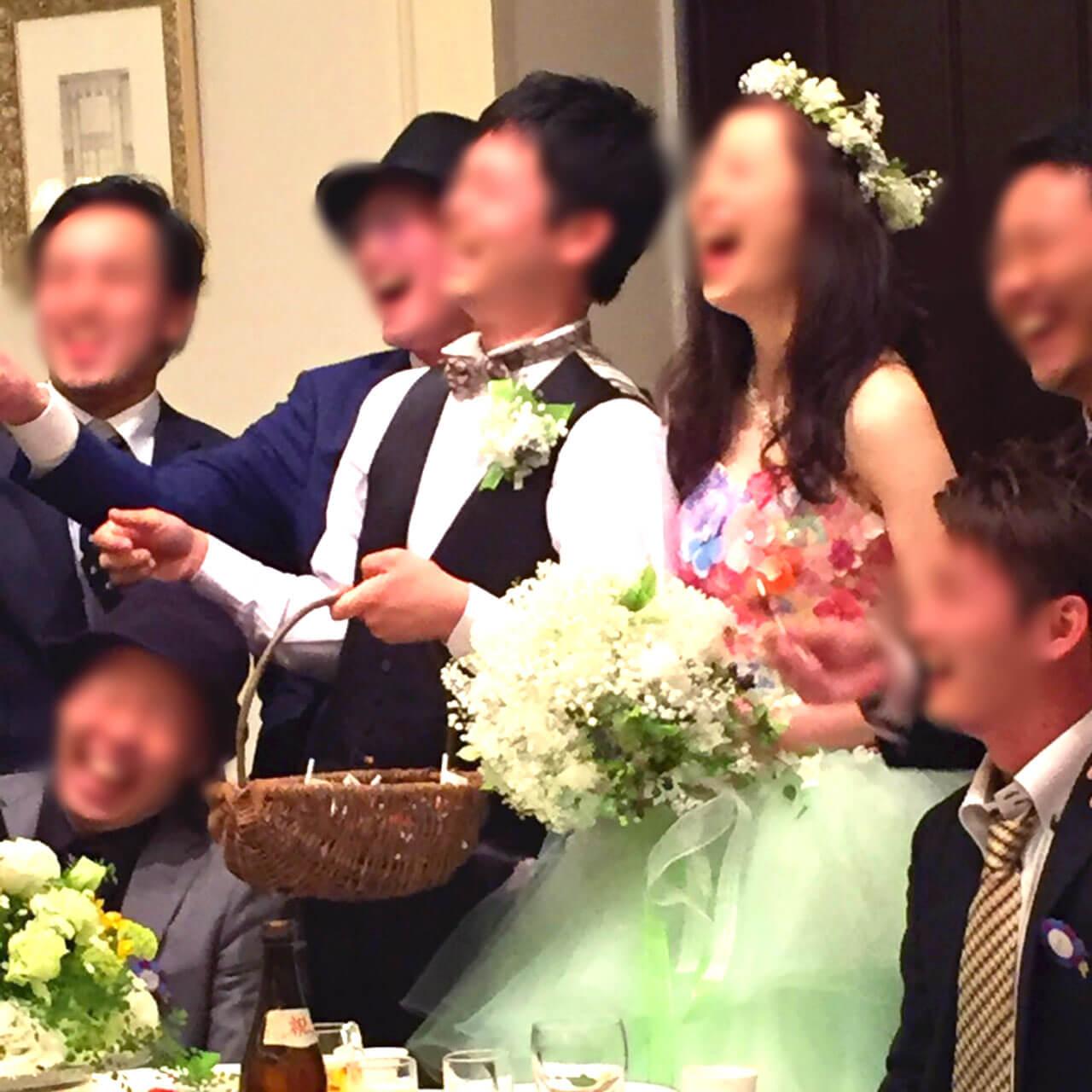 ウエストからしたがミントグリーン上が花柄の可愛いカラードレスを着た花嫁と新郎様。新婦様の手にある白いかすみ草の花束と、カールされた髪型の花嫁様の頭にグリーンのみや白のかすみ草の花冠がのっている。幸せそうな二人は、みんなに囲まれ笑っている笑っている