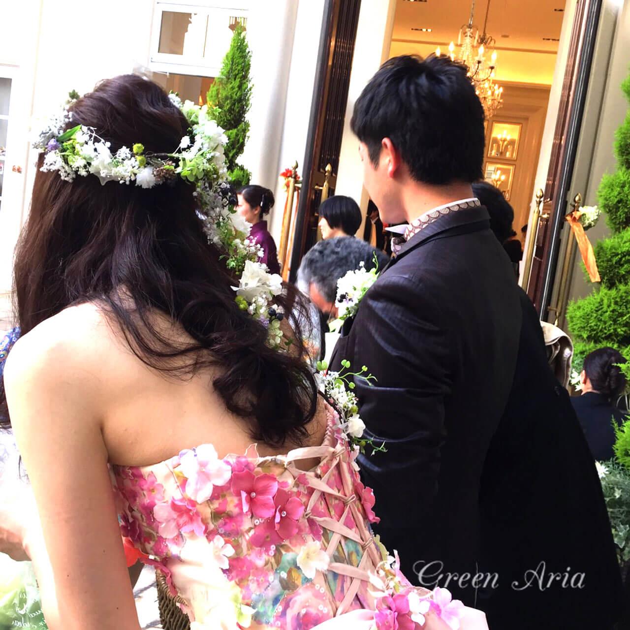 花柄のドレスにロングヘアーの新婦様のバックからの写真。白いかすみ草とグリーンやブルーの実の花冠。垂れ下がる花や実がとっともなちゅらるとってもナチュラル可愛い。