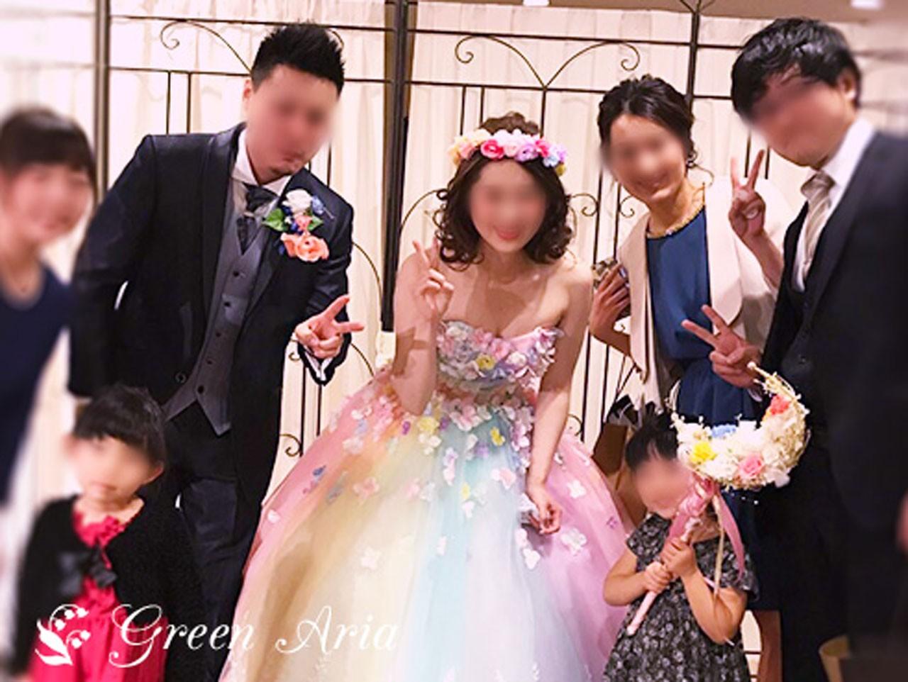披露宴の写真。沢山の友人に囲まれた新郎新婦。その前に、白に7色ローズのムーンスティックブーケをもった女の子