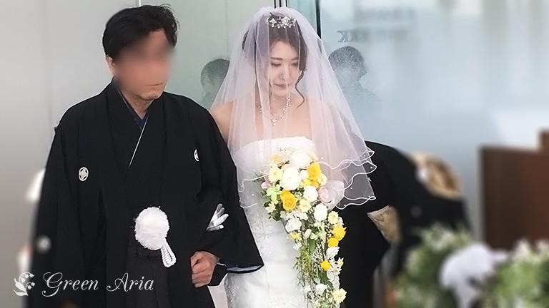 白いマーメイドドレスでお父さんとバージンロードを歩く花嫁様。花嫁様の手にはホワイトとイエローにグリーンの葉が入った流れるようなプリザーブドフラワーのキャスケードブーケ