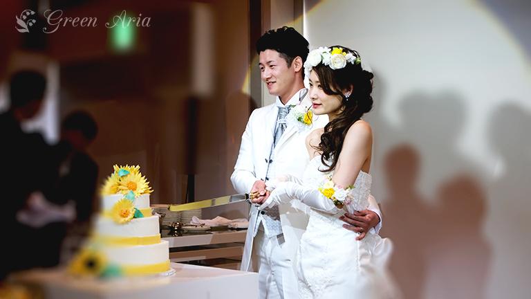 白いマーメイドドレスの新婦様に優しく手を当てる白いタキシードの新郎様。ケーキ入刀のシーン。花嫁様の頭には、白とイエローのバラが花冠のようにセットされ、左腕には、同じお花のアームレットがつけられている。