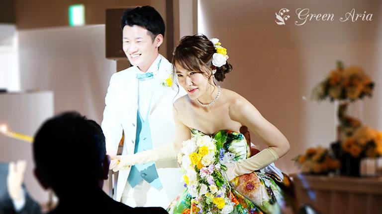 再入場でゲストテーブルを回る新郎新婦。しんぷは、グリーンベースにオレンジや白の花柄のドレスを身にまとい、ホワイトとイエローの揺れるブーケを持っている。