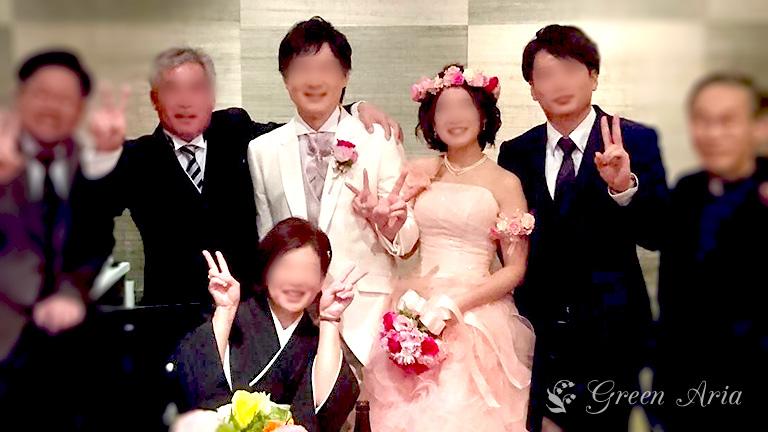 家族に囲まれて微笑む新郎新婦。パステルピンクのドレスの花嫁の手には、ピンクのグラデーションの丸いブーケ。おそろいのアームレットと花冠が可愛い。