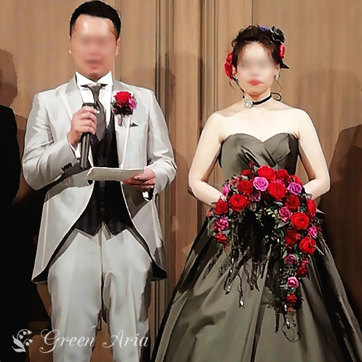 新郎の挨拶の場面。ライトグレーのタキシードの新郎は、マイクを持っている。隣の新婦は、カーキ家小野Aラインドレス。手には、赤いクレッセントブーケを持っている。