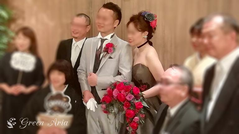 新郎新婦を囲み写真撮影。新婦の持つ赤い三日月形ウエディングブーケがとても華やか
