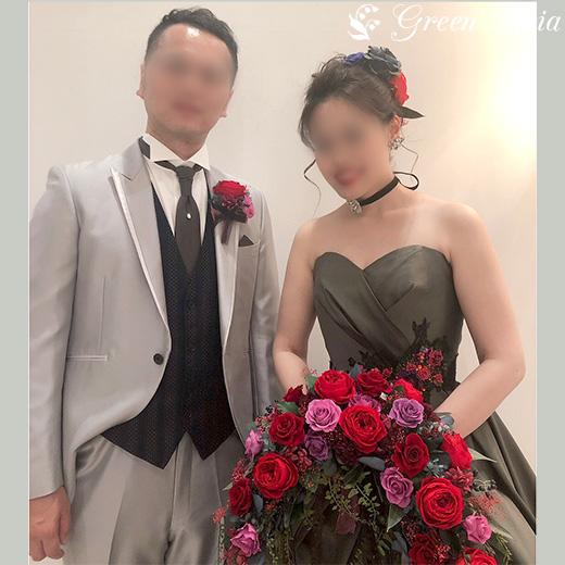 グレーのタキシード姿の新郎とカーキ色の胸元がハートになったドレス。反対色の赤い三日月形クレッセントブーケがとても豪華でドレスにマッチしている。