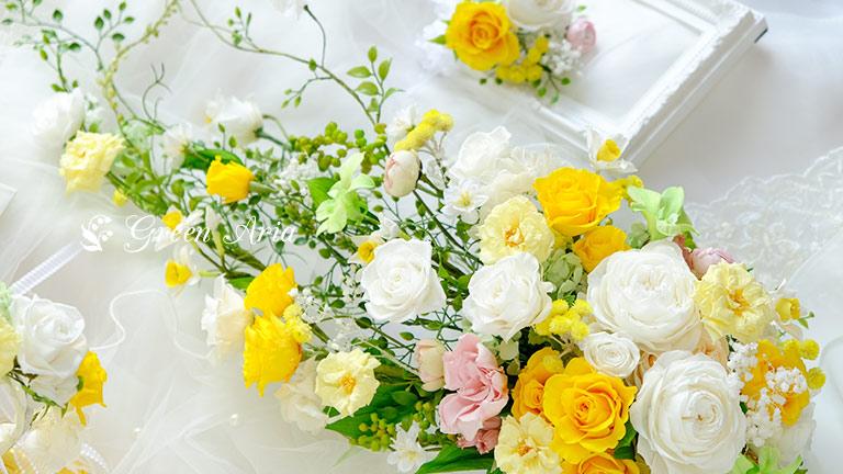 ホワイトとイエローのキャスケードブーケ。丸く大きなバラや小さなバラ、ランや水仙等可愛いお花のブーケで、丸い部分から垂れ下がるお花は繊細で、また、本物そっくりのリーフがエレガントである。