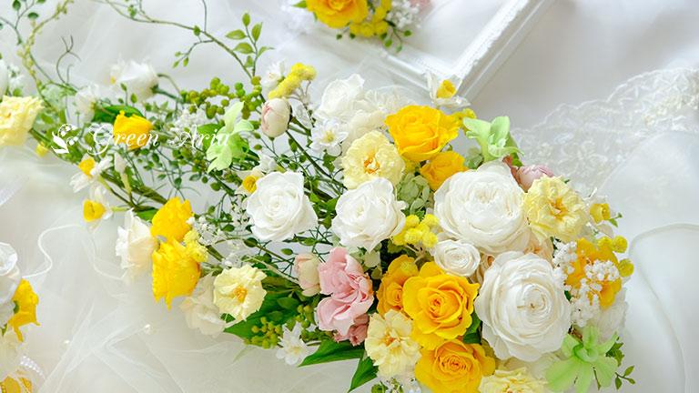 白の丸いバラと黄色のバラがメインの流れるように小花があるキャスケードブーケが斜めにおいてある。沢山のお花が入った可愛いウエディングブーケ。