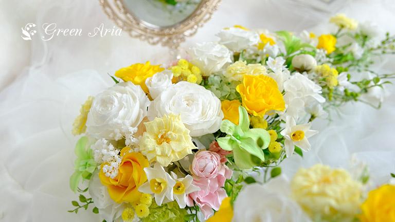 白い丸いバラとイエローのバラ、ライトイエローのひらひらしたバラ綺麗なグリーンのデンファレを使ったウエディングブーケ。頭を左下にし、斜めに移っている。