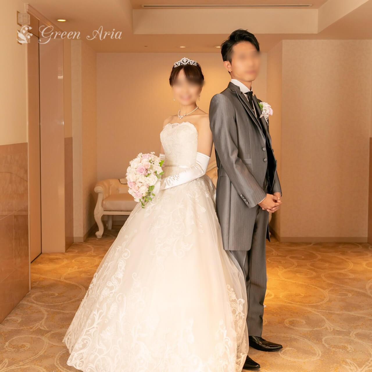 ソファーのある結婚式場で背を合わせてたつ新郎新婦。グレーのタキシードと白のAラインドレス。新婦の手には、しずく型の白とピンクのブーケ。