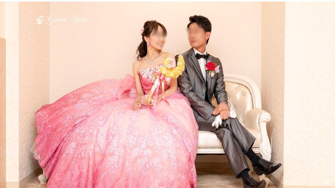 白いソファーに見つめ合って座る新郎新婦。ピンクのドレスの新婦様は、黄色の三日月にスティックが付いたブーケを持っている。三日月の中央にはレインボーローズが浮かんでいる。