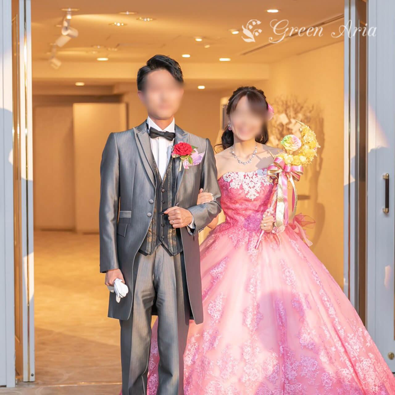 グレーのタキシードの新郎とピンクのドレスの新婦様。新婦様は、イエローの三日月の中にレインボーローズが浮かんだスティックブーケを持っている。披露宴の再入場の場面。