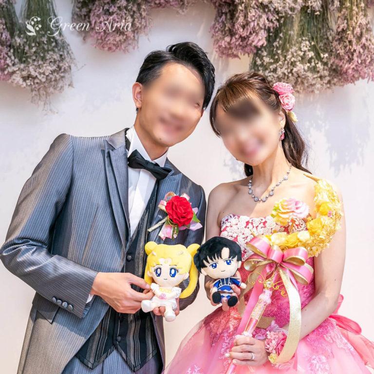 セーラームーンのマスコットを持ってにこやかに微笑む新郎新婦。新婦様は、三日月スティックブーケ、ムーンスティックを持っている。