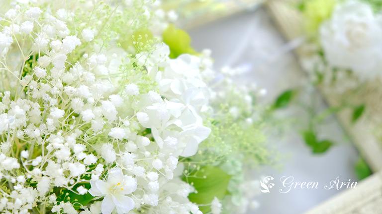 かすみ草ブーケの中に小さな白い花やグリーンのアジサイがあり美しい