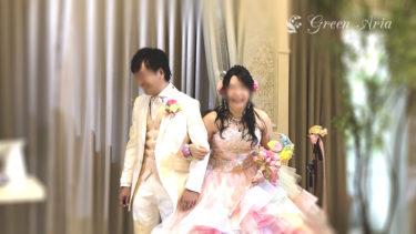 披露宴会場で明るく笑う花嫁さま。花嫁様は、レインボーカラーのプリンセスドレス。花嫁様の手には、虹色の月のムーンスティックブーケ。レインボーのバラも浮かんでいる。新郎様のブートニアもピンク・イエロー・ブルー・グリーンと華やか。