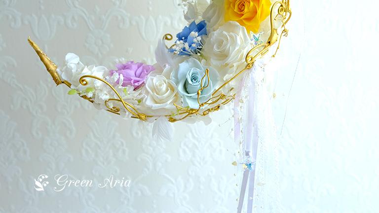 7色のバラが入った白い三日月形のウエディングブーケの半分から下の写真。白いレースやオーガンジー、サテンのリボンの合間から、流れるビーズや星形のスワロフスキーがキラリと光っている