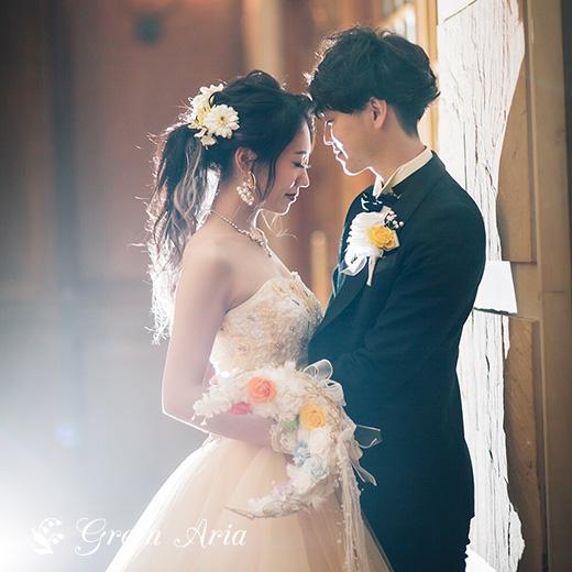 ライトイエローのカラードレスで髪を一つにまとめた新婦。新婦の手には、白い三日月形のブーケ。三日月の中には、7色のバラでとても可愛い。新郎は向かい合い、新婦の腰に手をあてている。バックからあたる照明でとても幻想的。