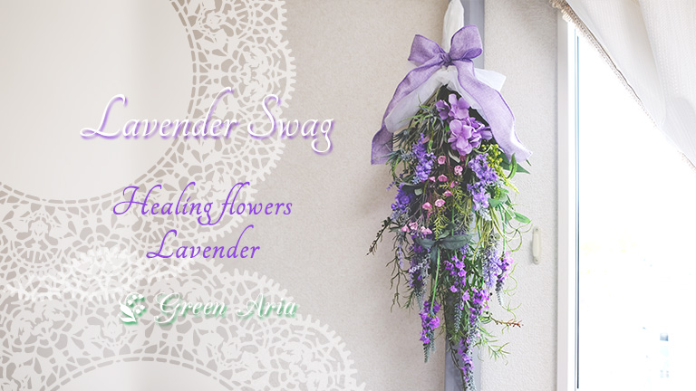 白い壁に掛けられた、ラベンダーの美しいスワッグ。いろんな紫の形状の違うラベンダーが入っていてエレガントなスワッグ