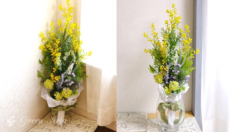 壁にミモザの花を上に向けて飾られた写真と、透明の花瓶にすっきり飾られたミモザのスワッグ。花束のように取り扱ってもいいですね。