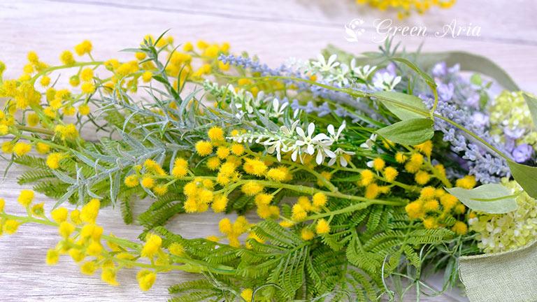 高級造花のアーティフィシャルフラワーで出来たミモザと白い穂状のベロニカライトブルーの小花がスタイリッシュなミモザのスワッグ。