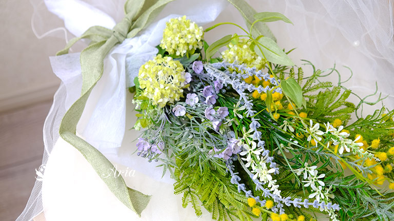 黄色のミモザの粒々、白い穂状のベロニカ、グリーンのアジサイ、ラベンダーのような紫の花、明るいグリーンの葉が花束のようにまとめられ、白いペーパーでラッピングされている。明るいグリーンのリボンがフレッシュさを出している。