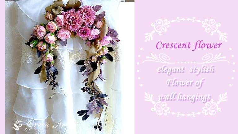 白いレースの背景にかけられたピンクのバラが沢山入ったクレッセントのアレンジメント