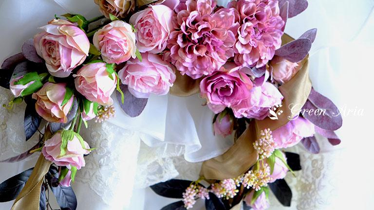 モーブピンクのダリアを中心に左右にバラが流れて美しいフラワーアレンジメント。アンティークでモーブな印象。