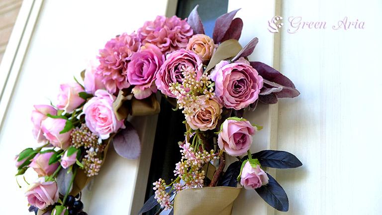 白いドアにかけられたアンティーク調のバラが美しいクレッセントのフラワーアレンジメント。