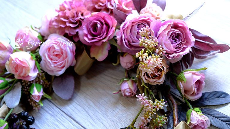ライトピンク、青みピンク、モーブピンクのバラが美しいフラワーアレンジメントの壁掛け。キラキラ光るラメ入りバラも魅力的