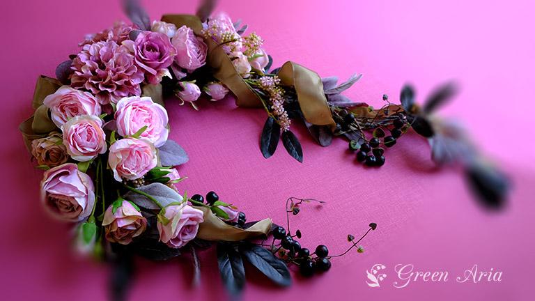 高級造花の美しいバラが入ったアレンジメント。壁にかけられて置く場所がなくてもOK。ピンクのいろいろなバラが入ってエレガントな印象。