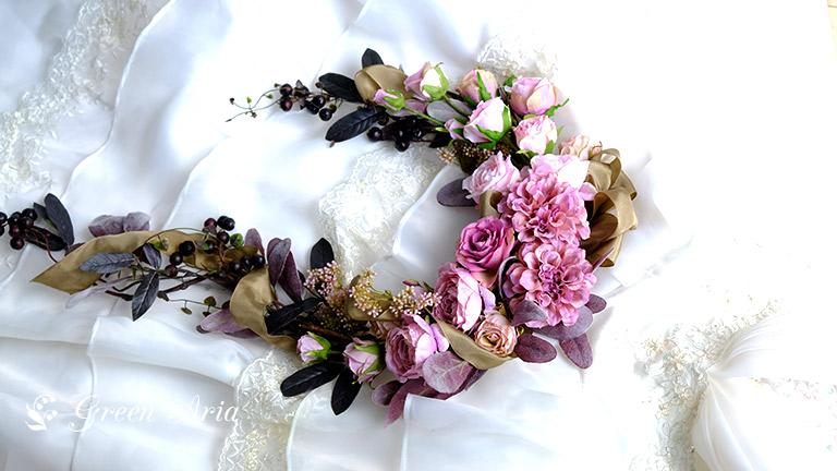 白いドレスの上のアンティークな造花のアレンジメント。ピンクと濃い色の葉が魅力的。
