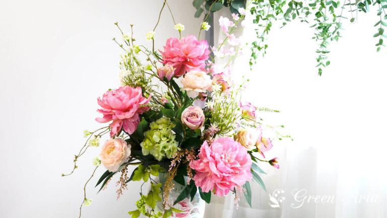 ピンクの芍薬とグリーンのあじさい、ピンクのバラやオレンジのラナンキュラスが美しいフラワーアレンジメント。テーブルの上に置けば空間がぱっと明るくなる。