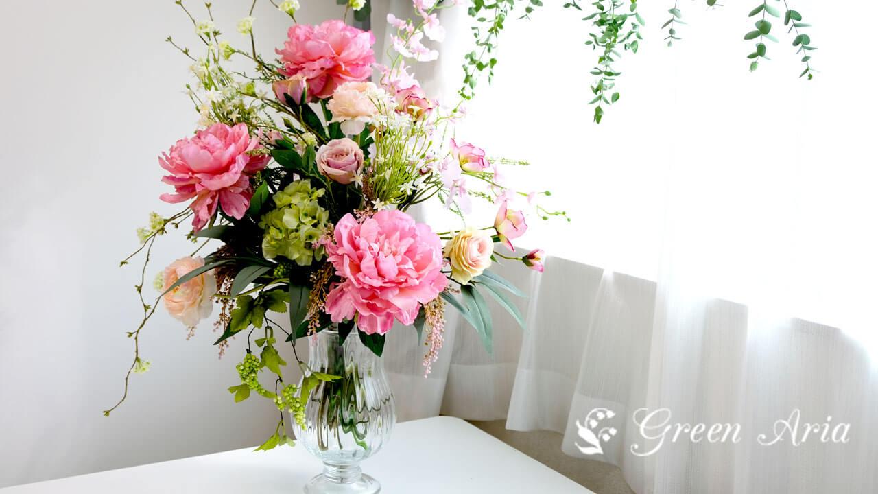 透明なガラスの花瓶に入った芍薬がメインのアレンジメント。窓辺に飾られたピンクとグリーンのフラワーアレンジメントが光が当たって美しい