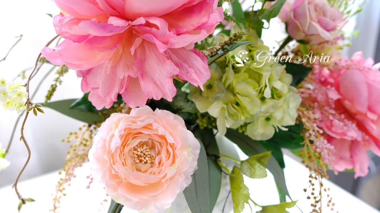 オレンジのラナンキュラスとピンクの芍薬がとても美しいフラワーアレンジメント。白い小さな星のようなオオアマナの花が光りに当たって綺麗。