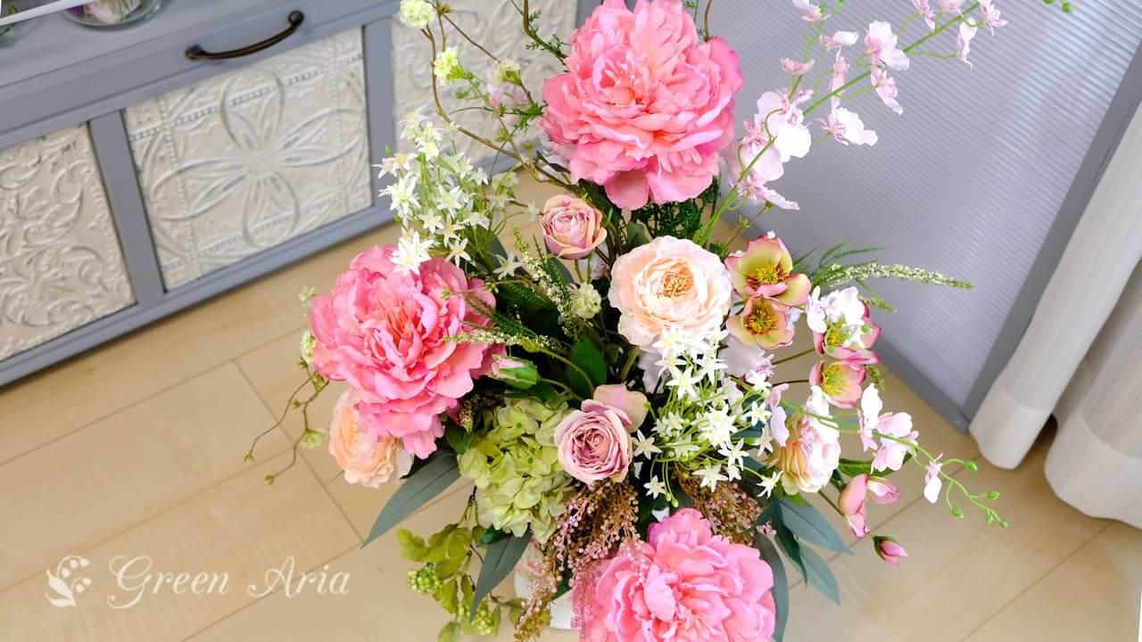 ピンクの芍薬とラナンキュラスバラが入った花束状のアレンジメント。とても華やかなのでプレゼントによさそう。