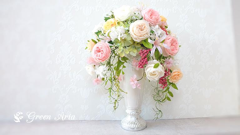 白い器にホワイト、アイボリー、ピンク、イエローの花が左右に流れている。垂れ下がる葉っぱも繊細で上品。濃いピンクの丸い実の集まりのペッパーベリーがよりかわいらしさを生み出している。