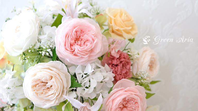 ピンクのオールドローズとホワイトのオールドローズ、間にアジサイやアーティフィシャルフラワーの葉っぱが見えている。プリザーブドフラワーアレンジメント。